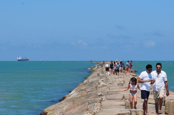 People on breakwater at Isla Blanca Park, South Padre Island, Texas